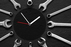 Clock of wrenches on black textured background. Clock of the shiny wrenches on black textured background Stock Photos