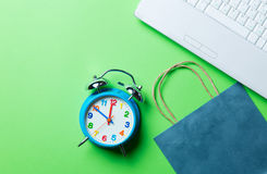 Clock, shopping bag and laptop. Clock, blue shopping bag and laptop on the green background Stock Images
