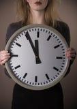 Clock showing five to twelve Stock Photos