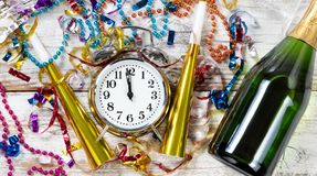 Close up of clock showing Midnight for Celebration of New Year H. Clock showing Midnight for New Year celebration surrounded by party objects and Champagne royalty free stock photography
