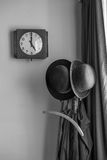 A clock showing 5 o'clock next to bowler hats on a stand Stock Image
