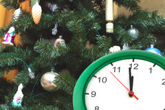 Clock showing twelve hours and dressed up Christmas tree Stock Photos