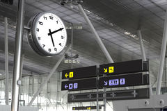 Clock and signs at an airport Royalty Free Stock Images