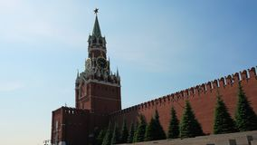 Clock on Spasskaya Tower of the Kremlin against the blue sky on a sunny summer day. Red Square in Moscow, the capital of. Clock on Spasskaya Tower of the Kremlin stock footage