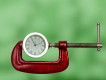 Clock squeezed with clamp. Stock Photo