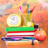 Clock and stand for pencils on stack of books Royalty Free Stock Images
