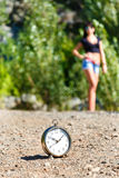 Clock on the stone road and blurred girl at sunny day. Clock on the stone road and blurred brunette girl on a sunny day. time to travel concept Stock Photos