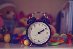 Clock surrounded by colorful toys Stock Photography