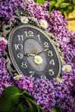 Clock surrounded by spring flowers. Shallow depth of field with selective focus on clock. Lilac flowers Stock Photography