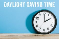 Clock on table with Daylight Saving Time message. Daylight Saving Time written on wall behind clock turned to 2am royalty free stock image