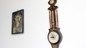Clock, thermometer and orthodox icon hanged on a wall Stock Photography