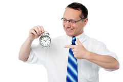The clock is ticking, achieve your target. Smiling businessman holding an alarm clock Royalty Free Stock Photography