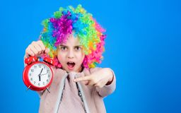The clock ticking away the time. Adorable small child with colorful wig hair pointing at alarm clock for the exact time. Time concept. Time your clock with royalty free stock images