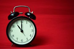 Clock ticking to 11 o`clock on the red background stock images