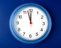 Clock about to hit midnight or noon on blue backgr. Time - Clock about to hit midnight or noon on blue background Stock Photography