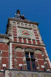 Clock Tower. A portion of a building in Amsterdam, The Netherlands, that show Dutch architecture of the period. The photo contains a blue sky background Royalty Free Stock Image
