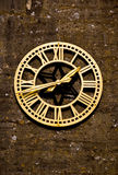 Clock tower. An image of a very old bronze clock on an old wall with lichen attached royalty free stock photo