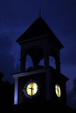 Clock Tower. A glowing clock tower against a dark blue hazy sky royalty free stock photo