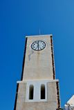 The clock on the tower. The old clock on the tower still underway. They continually remember the story of this island, and store it Stock Image