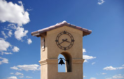 Clock Tower. With bell on blue sky with white clouds Stock Image