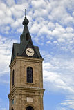 Clock tower. On the blue cloudy sky background Royalty Free Stock Image