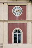 Clock on tower. Above an arched window on an exterior building facade with a painted red inset royalty free stock images