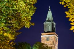 A clock tower of cathedral in Turku, Finland. A clock tower of cathedral in Turku, Finland with blurred leaves on a foreground stock photos