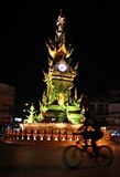 Clock Tower in Chiang Rai, Thailand. Nightly light show in Chiang Rai, Thailand, with the tower lighting up with many different colors and music. Girl rides Royalty Free Stock Photo