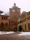 Clock tower in a German Castle. A taste of the old world with a classic German clock tower overlooking a stone castle courtyard.  A light dusting of snow Royalty Free Stock Image