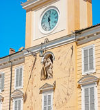 The clock tower of Governor Palace in Parma. The clock tower of the Governor Palace in Parma decorated with the stone sculpture of Virgin Mary, surrounded by Stock Photo