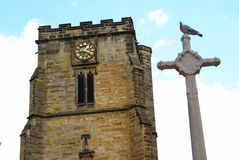 Clock tower of medieval cathedral with dove. Sitting on a cross in the foreground Stock Photography