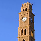 Clock tower in old Akko. With faces in Hebrew and Arabic, crowned with Israeli flag stock image