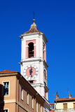 Clock Tower in the Old in Nice. Over the roofs of the town clock tower rises against a blue sky Stock Photo