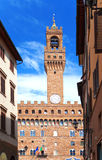 The clock tower of the Old Palace (Palazzo Vecchio) in Signoria Square, Florence (Italy) against the blue sky Stock Photo