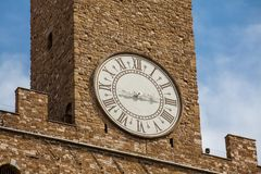Clock tower of the Palazzo Vecchio built at the Piazza della Signoria in the 12th century in Florence. The clock tower of the Palazzo Vecchio built at the Piazza stock photography