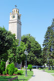 The Clock Tower and Park. The Clock Tower and city park in Bitola, Macedonia. Walkway with benches and lanterns is leading to the tower Royalty Free Stock Image