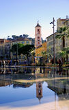 Clock Tower Ryusuke in Nice. Clock Tower Ryusuke ​​is reflected in the lake of the promenade area in the heart of Nice Stock Image