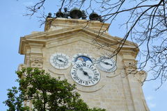 Clock tower. With several clockcs behind the trees on Malta Royalty Free Stock Image