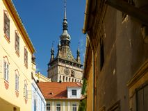 The clock tower from Sighisoara as seen from a street with colorful houses from the medieval fortress Royalty Free Stock Photography