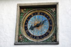 Clock tower in solar style on relief with scribes. Tallinn, Estonia - September 1, 2017: Architectural details on old building. Chiming clock on tower in solar royalty free stock photos