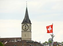 Clock tower of the St. Peter Church and Swiss Flag on the facade. Building in Zurich, Switzerland Royalty Free Stock Photos