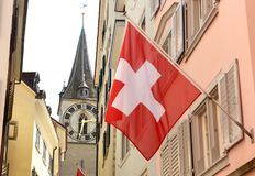 Clock tower of the St. Peter Church and Swiss Flag on the facade. Building in Zurich, Switzerland Royalty Free Stock Images