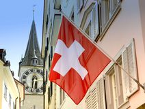 Clock tower of the St. Peter Church and Swiss Flag on the facade. Building in Zurich, Switzerland Stock Photography
