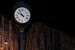 Clock tower on street park night with bokeh lighting gold yellow background romantic nightlife. The clock tower on street park night with bokeh lighting gold stock photos