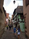 Clock tower and traditional Houses with colorful facades and sloping roofs in Riquewihr, France. stock photos