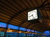 Clock in trainstation. Platform of the Haarlem trainstation with clock displaying 8:27 AM. Blue purple sky behind the yellow roof with steel arches construction Stock Photos