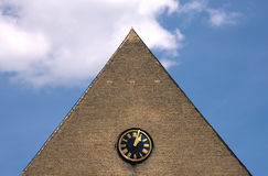 Clock on triangular wall Stock Images