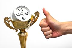 A clock in a trophy with thumbs up. Representing good time management royalty free stock photo