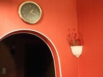 Clock and vase with roses in the red corridor. Under artificial lighting Stock Images