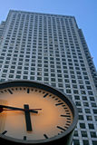 Clock with very tall steel office building. Looking up a clock with very tall steel office building in the background stock photos